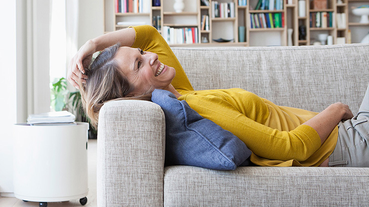 Frau liegt auf dem Sofa in heller Wohnung