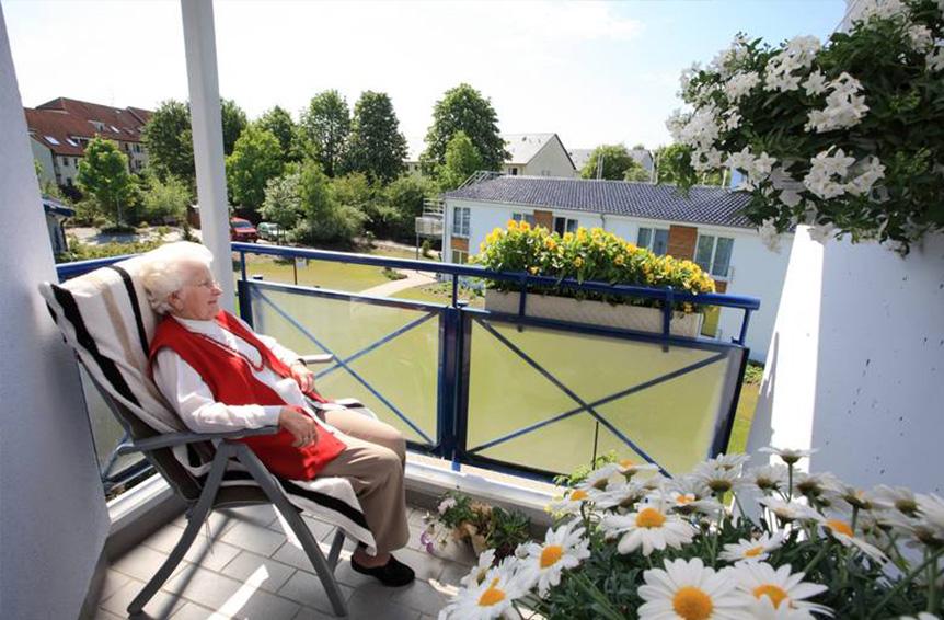 Alte Dame auf sonnigem Balkon.