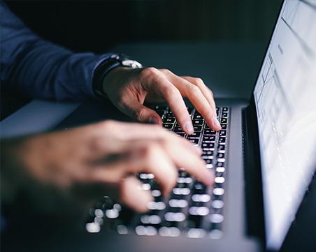 Mann tippt auf einem Laptop.