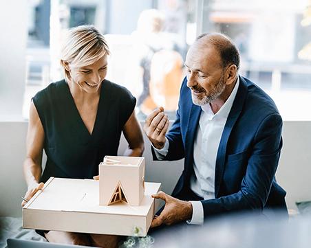Zwei Personen diskutieren ein Architekturmodell.