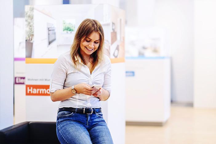 Mitarbeiterin sitzt auf der Lehne eines Sofas und schaut auf ihr Smartphone