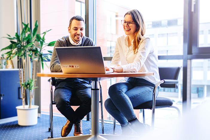 Zwei Mitarbeiter sitzen am Tisch und schauen gemeinsam auf den Laptop