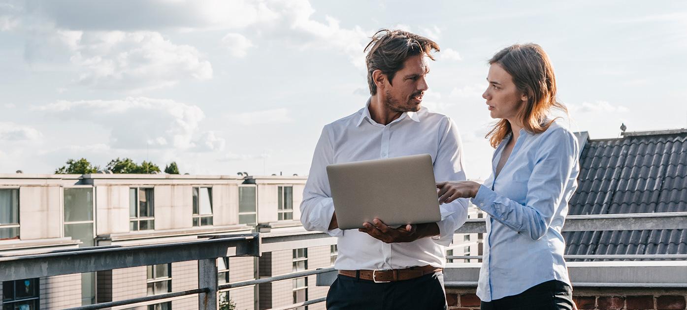 Zwei Kollegen diskutieren an einem Laptop.