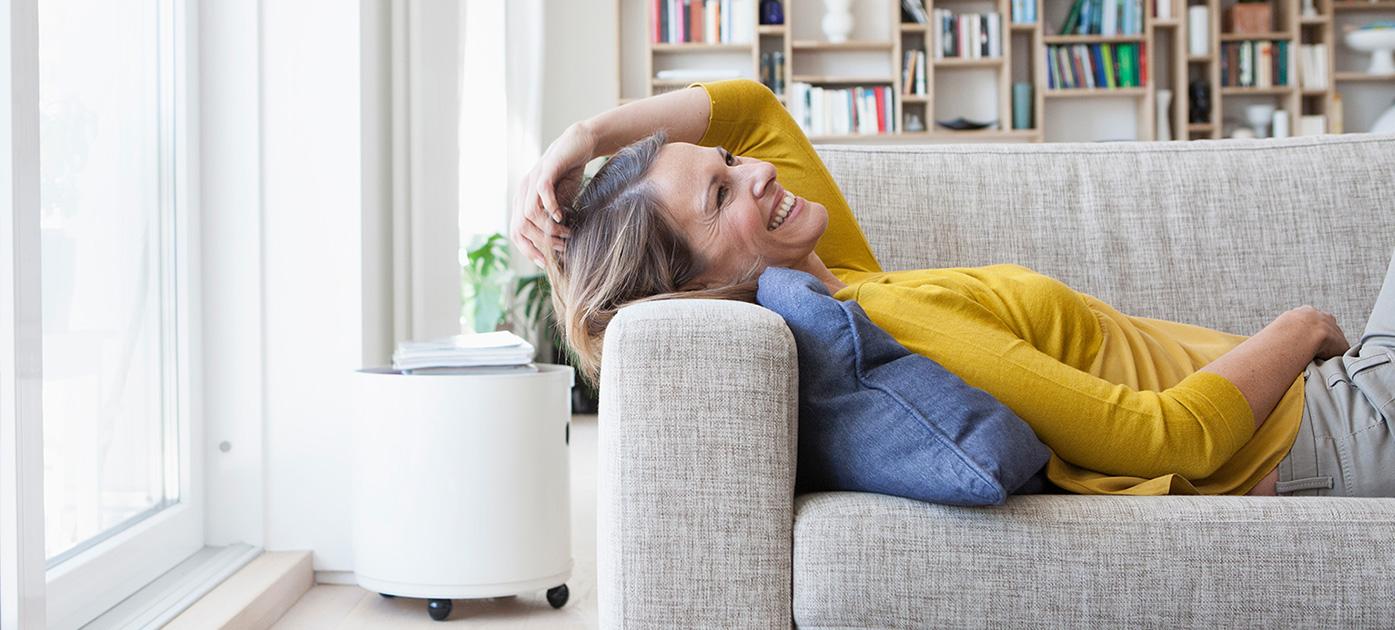 Lachende Frau liegt auf einem Sofa.