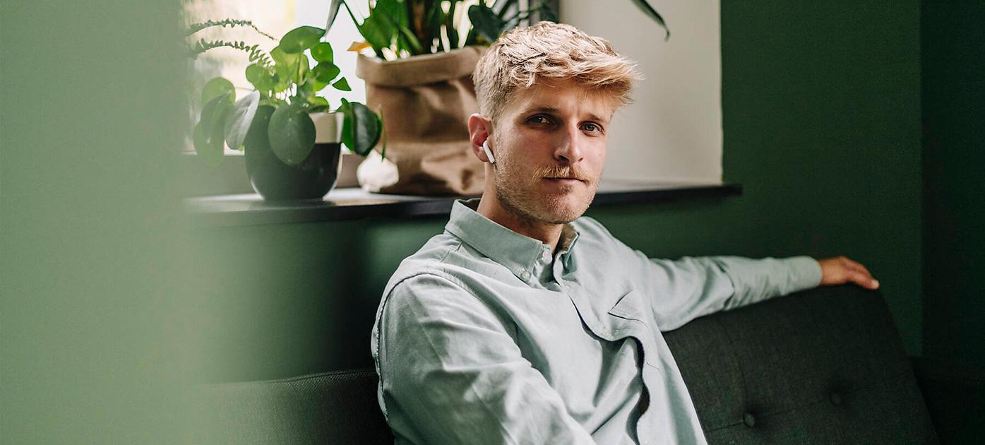 Mann mit Kopfhörern sitzt auf einem Sofa