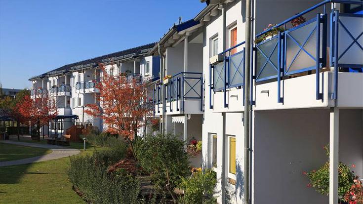 Sonnige Häuserzeile mit Balkons.
