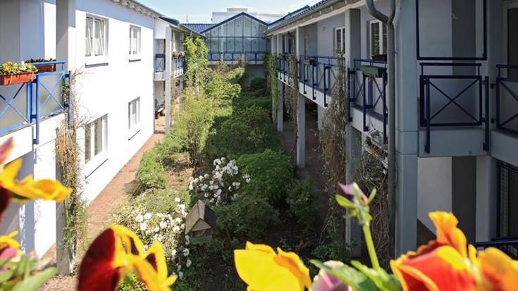 Gartenanlage zwischen zwei Häuserzeilen.