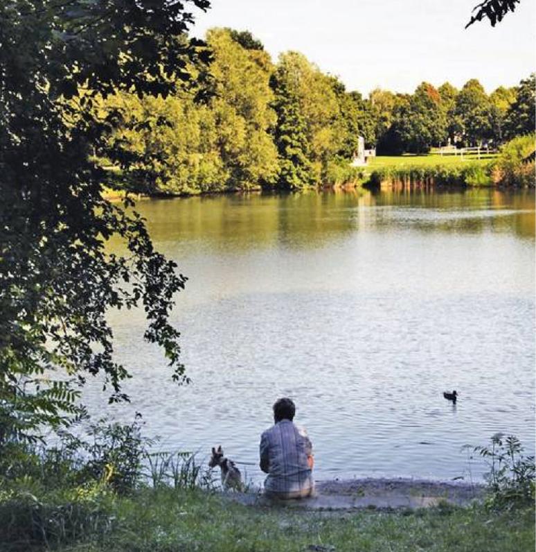Mann sitzt an einem Seeufer.