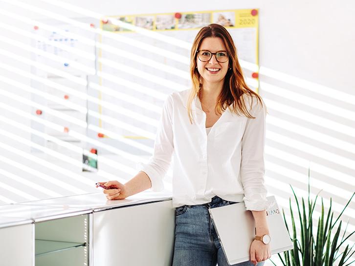 Frau steht am Tresen im Büro und lächelt in die Kamera