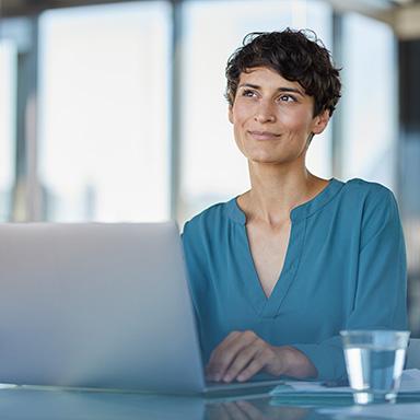 Frau am Laptop blickt in die Ferne.