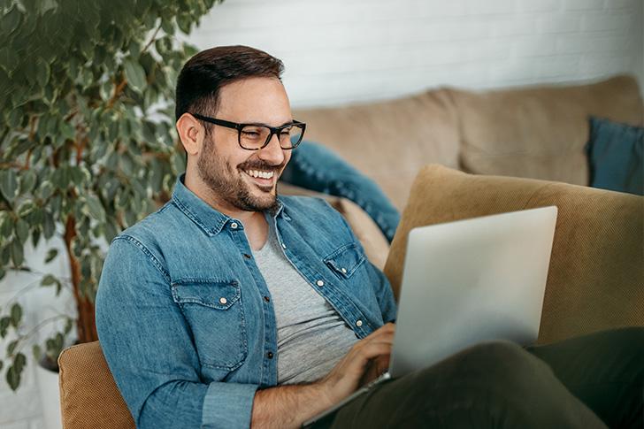Mann sitzt auf der Couch mit Laptop auf dem Schoß