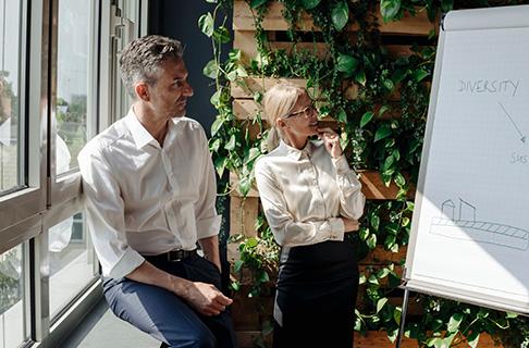 Frau und Mann an einem Whiteboard.