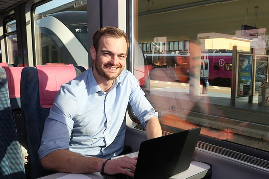 Mitarbeiter im Zug am Laptop.