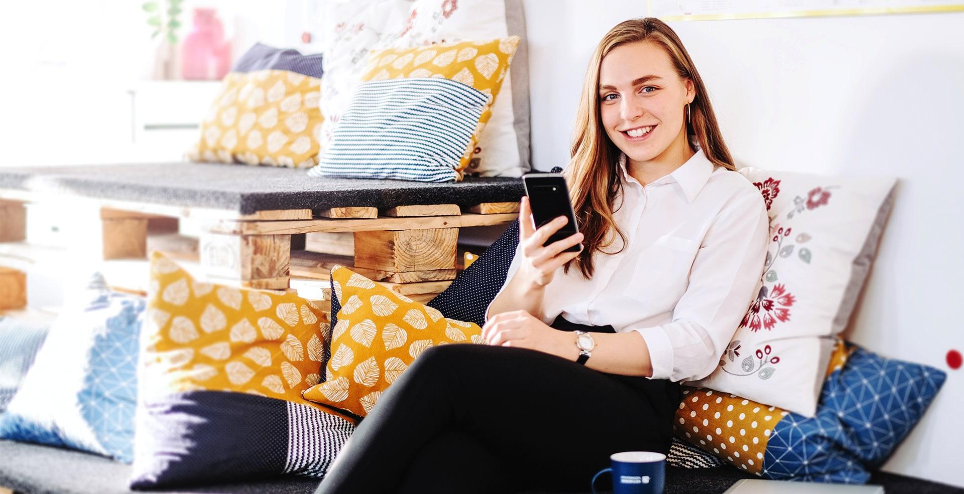 Mitarbeiterin auf der Couch mit Smartphone in der Hand.
