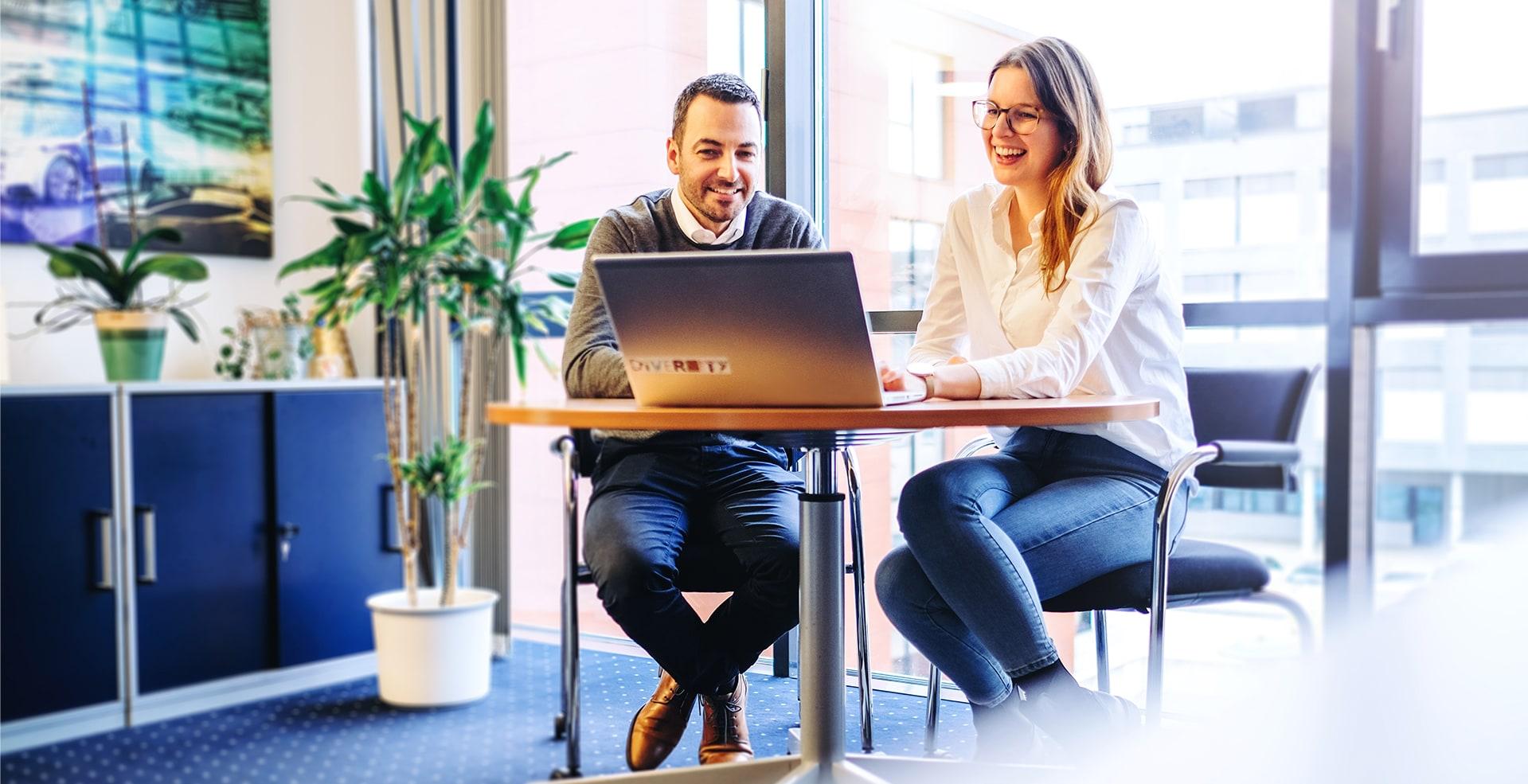 Zwei Kollegen im Meeting mit Blick auf dem Laptop.