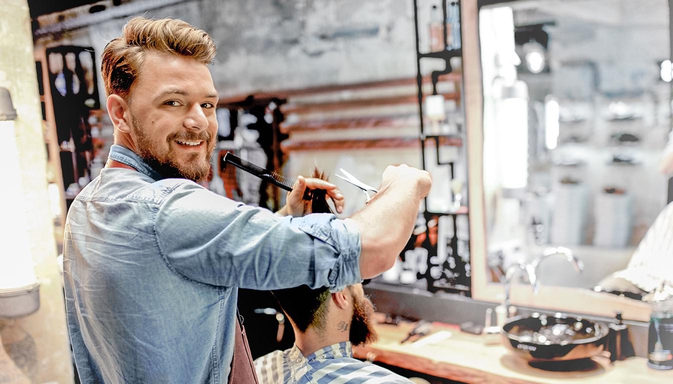 Friseur schneidet einem Kunden die Haare.