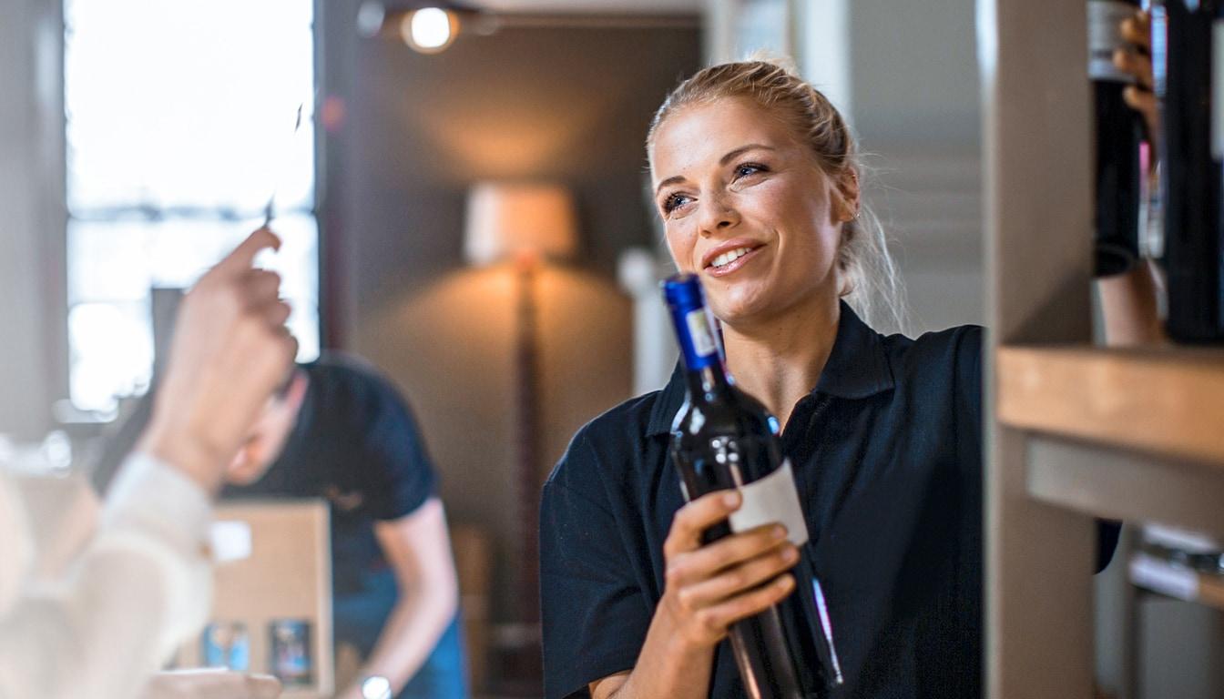 Mitarbeiterin in einem Delikatessenladen verkauft Wein an Kunden.