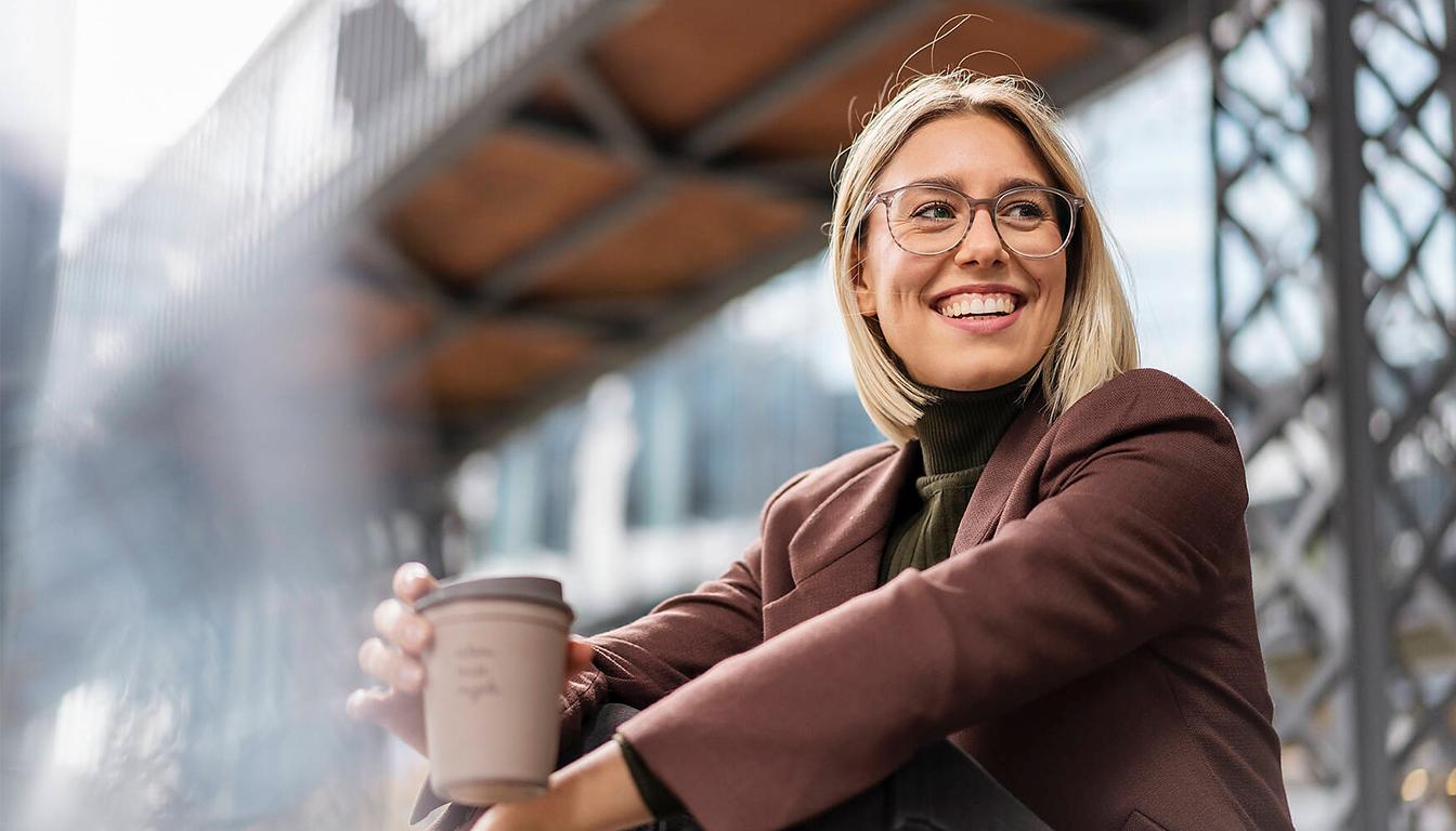 Businessfrau mit einem Kafeebecher in der Hand.