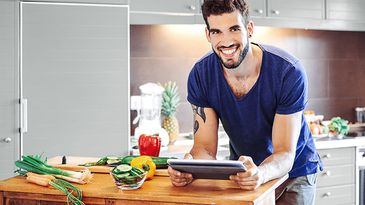 Student steht in einer Küche mit Tablet in der Hand.
