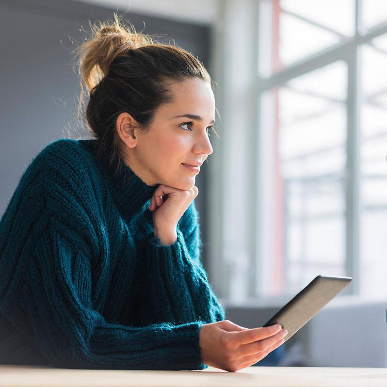 Lächelnde Frau sitzt am Tisch mit Tablet in der Hand