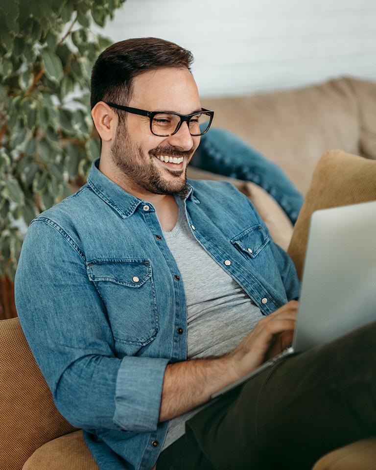 Lächelnder Mann sitzt auf dem Sofa mit Laptop auf den Beinen