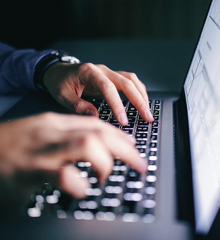 Nahaufnahme von tippenden Händen auf einen Laptop